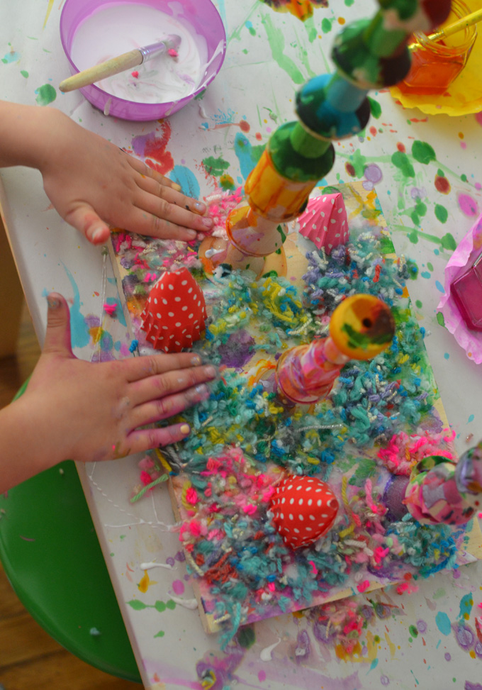 Children make mixed-media wooden sculptures using wood pieces, liquid watercolor, are yarn.