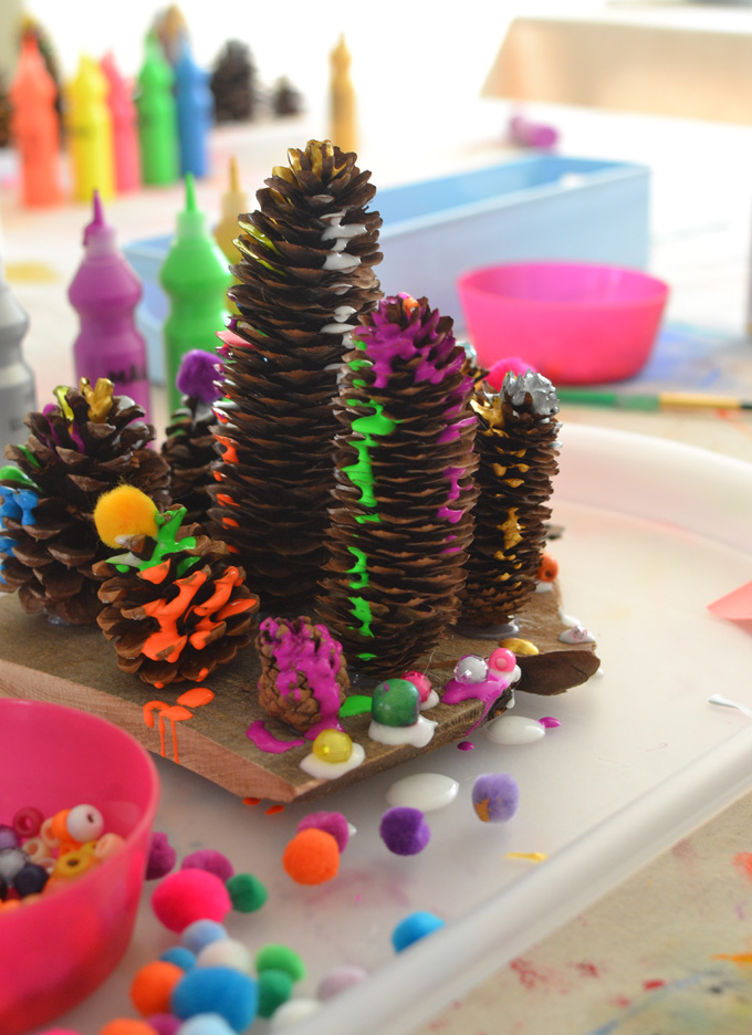 Kids use a drip paint technique to embellish pinecones and create a drippy forest.