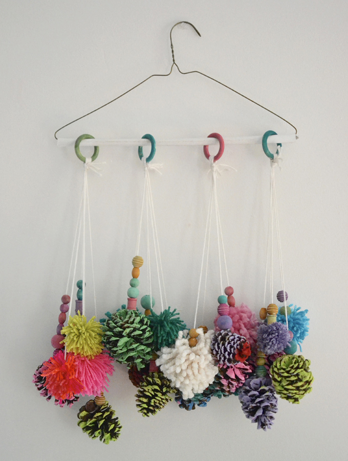 Children paint pinecones and make pom-poms then hang them from a wire hanger to create some art for the wall.
