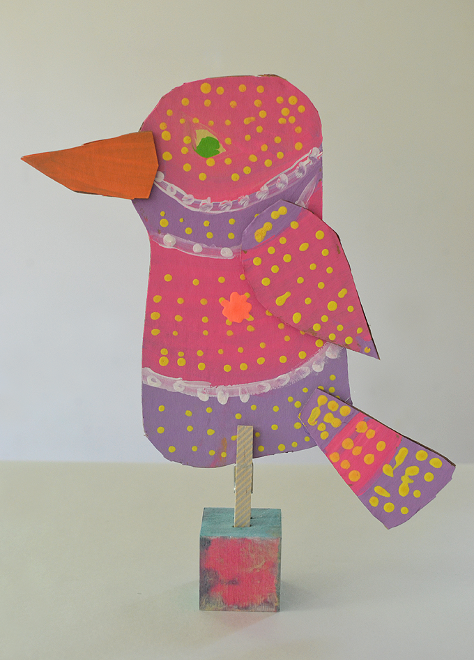 Kids make cardboard birds and attach them to wooden blocks for display.
