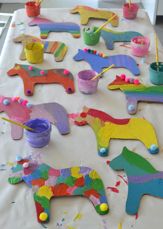 Kids paint cardboard Swedish dala horses at a birthday party.