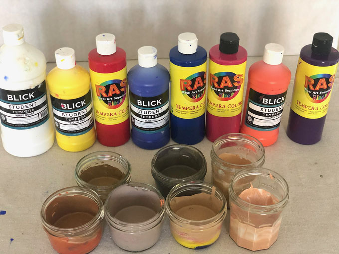 Using primary color tempera paints to mix skin tones for art class.