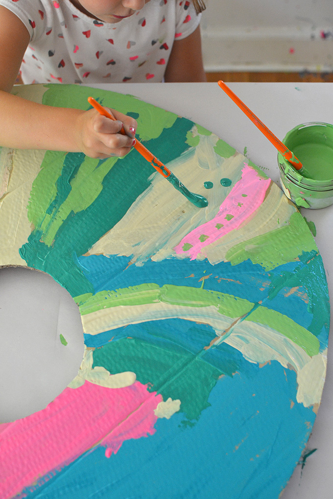 Mixing paint colors using tempera paints to paint giant cardboard donuts.