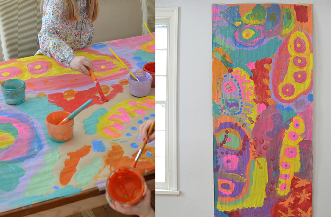 Painting on a table covered in butcher paper using tempera paints.