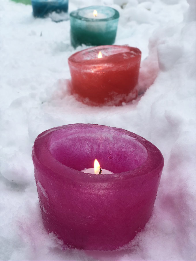 Make simple ice votives by freezing water overnight in a deli container and adding some food coloring. A beautiful addition to your outdoor, pandemic party!